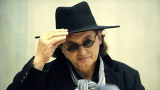 Marc Veyrat, seen holding a wide-brimmed black hat and wearing dark sunglasses