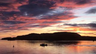 A sunset over Oban Bay with boat in forefront