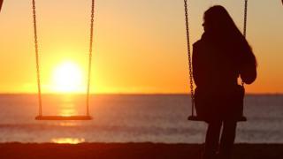 Mujer frente al mar al lado de un columpio vacío