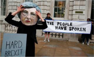 A demonstrator wears a mask depicting Theresa May