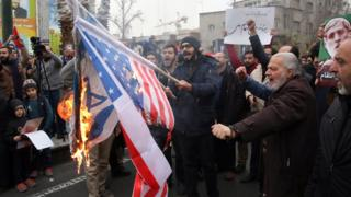 Iranians burn US and Israeli flags during anti-US protests over killing of Qasem Soleimani in Tehran, 4 January 2020