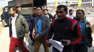 Nepali football players are escorted by security personnel to a court in Kathmandu