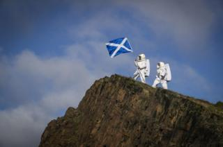 Actors Joy Maria Onotu (left) and Sarah Miele, stars of the Edinburgh Fringe show 'Valentina's Galaxy' take their first steps on what looks like a new planet but is in fact the Salisbury Crags in Holyrood Park above the city of Edinburgh, 15 August 2019.