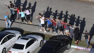Imagens mostram estudantes sendo evacuados em grupos pequenos após massacre na Flórida