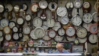 A watch and clock vendor sits in his shop in Seoul on 29 July 2015