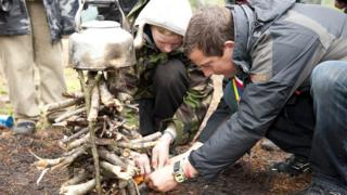 Chief scout Bear Grylls helping youngsters with lighting a fire