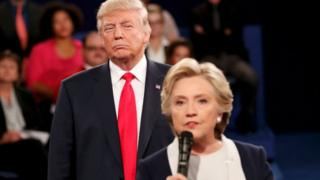 Donald Trump listens as Hillary Clinton answers a question during presidential debate at Washington University in St Louis, Missouri, U.S., October 9, 2016