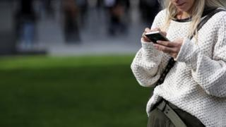 Technology A woman uses her mobile phone in Spain
