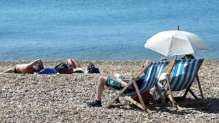 People enjoy the warm weather on the beach in Brighton, East Sussex