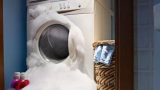 Máquina de lavar roupa com espuma saindo pela abertura frontal