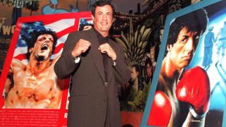 Сильвестр Сталлоне на фоне изображений марок, посвященных его знаменитому фильму