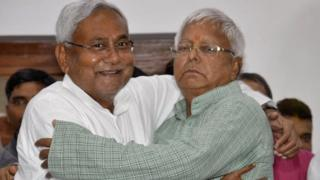 Nitish Kumar (L), a leader of Janata Dal (United) and Chief Minister of eastern state of Bihar, hugs Lalu Prasad Yadav, chief of Rashtriya Janata Dal, before addressing a news conference in Patna