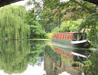 A canal boat reflected in water