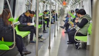 Commuters read books on the underground in China