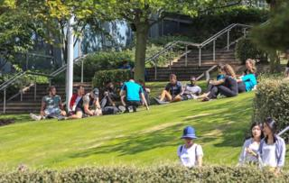 People enjoy the sunshine at Chavasse Park in Liverpool