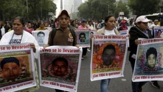 Relatives hold pictures of some of the 43 missing students of Ayotzinapa College Raul Isidro Burgos during a march in Mexico City.