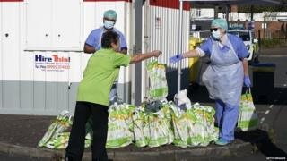 Asda care worker handing over food bag to NHS worker at temporary testing site in Wolverhampton