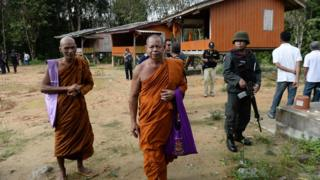 Buddhist monks pass an armed Thai police officer assigned with securing the compound of Rattanaupap temple in Narathiwat province, 19 January 2019