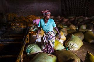 A woman holds a knife as she works with sacks containing palm oil at the Crystal Soap factory in Butembo