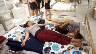 Người ta ngủ trưa trên giường tại một cửa hàng Ikea để tránh cái nóng bên ngoài ở Hàng Châu, Trung Quốc, năm 2017.