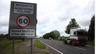 A lorry crosses the border from Northern Ireland to the Republic of Ireland passing a road sign welcoming drivers to Northern Ireland.