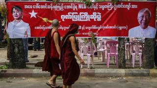 Monks pass in front of an NLD banner celebrating Myanmar's new President Htin Kyaw
