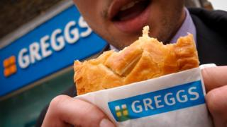 Man eating Greggs pasty