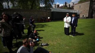 Fatima Boudchar, wife of Libyan politician Hakim Belhadj, stands with their son Abderrahim, as she holds a letter of apology from Prime Minister Theresa May outside the Houses of Parliament in Westminster
