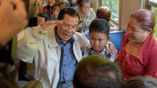 Cambodian Prime minister Hun Sen (L) talks with passengers on a train at the Phnom Penh train station on April 30, 2016, as the railway service resumes after years of suspension.