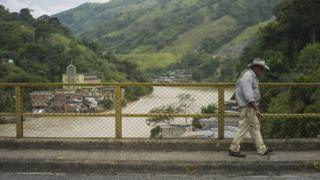 A man walks over a bridge over the river Cauca