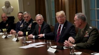 U.S. President Donald Trump reaches out to touch the arms of Chairman of the Joint Chiefs of Staff Joseph Dunford (R) and U.S. Defense Secretary Jim Mattis (C) while delivering remarks during a meeting with military leaders