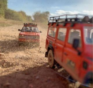 in_pictures Red model Land Rovers driving along dirt track
