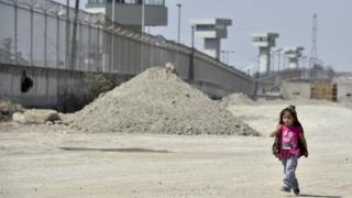 "A girl walks along the perimeter wall of the El Altiplano prison, where Mexican drug lord Joaquin ""El Chapo"" Guzman is being held, on February 24, 2016 in Almoloya de Juarez, Mexico. AFP"