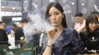 A woman exhales vapor while smoking an electronic cigarette during the 2019 IECIE Shenzhen eCig Expo at Shenzhen Convention and Exhibition Center on April 14, 2019