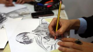An artist draws a manga-style illustration at a stall during the Libya Comic Convention, in the capital Tripoli on 2 November 2017