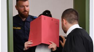جنيفر و. أثناء دخولها المحكمة وقد حجبت وجهها بملف كبير