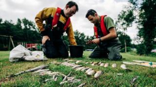 two men sorting through dead fish