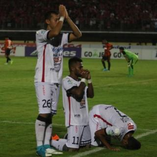 Footballers for Bali United FC assume three different prayer positions