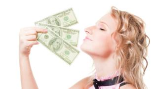 Una mujer disfrutando del aroma del dinero