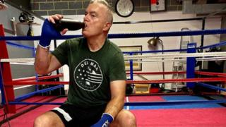 Huw Edwards drinking water outside a boxing ring