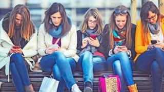 مجموعة من الفتيات يتصفحت هواتفهن المحمولة