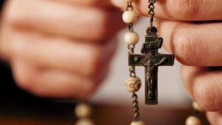 A person holds a rosary