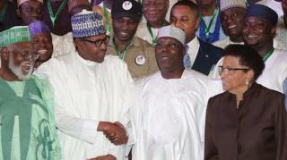 Muhamadu Buhari (hagati i bubamfu) na Atiku Abubakar (hagati i buryo) bahana ukuboko aho bari baje gushira umukono ku masezerano y'amahoro imbere y'amatora, itariki 13/02/2019
