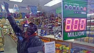 An optimistic lottery ticket buyer in New Jersey shows off his Power Ball ticket through a shop window (09 January 2016)
