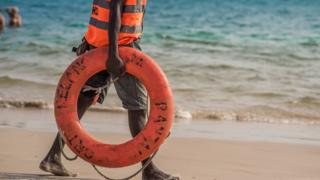A lifeguard holding a lifebuoy on the beach in Lagos, Nigeria