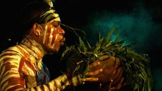 A dancer in Aboriginal dress blows smoke from a bowl filled with leaves.