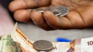 A hand holding Ugandan currency