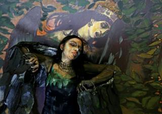 Model Alyona Alekseitseva presents a body of artwork by Russian artist Maria Gasanova, in Krasnoyarsk, Russia. Behind is a reproduction of Victor Vasnetsov's Sirin and Alkonost: A Song of Joy and Sorrow. 24 October, 2018