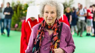 Margaret Atwood, The author of The Handmaid's Tale Walks though the Hay festival followed by handmaids from here famous book