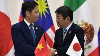 Bộ trưởng Công thương Trần Tuấn Anh (trái) bắt tay với Bộ trưởng Tái thiết Kinh tế Nhật Bản Toshimitsu Motegi sau buổi họp báo về TPP trưa 11/11